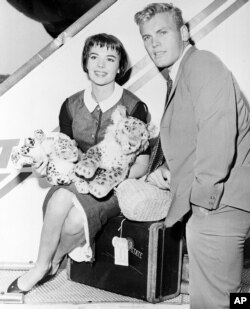 Actress Natalie Wood, left, and actor Tab Hunter pose at the TWA baggage claim at Idlewild Airport in New York City, after arriving from Los Angeles, Aug. 21, 1956.