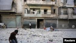 Thường dân bên ngoài một tòa nhà bị trúng đạn pháo kích từ các lực lượng chính phủ Syria ở phía bắc thành phố Aleppo, ngày 25/8/2012