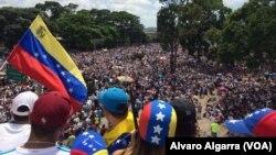 Seorang penentang Presiden Nicolas Maduro melambaikan bendera nasional saat ribuan orang memblokir jalan raya utama di Caracas, Venezuela, hari Sabtu, 20 Mei 2017 (foto: Alvaro Algarra/VOA)