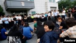 Keluarga korban kapal ferry Sewol duduk di depan sebuah bangunan dimana para awak kapal ditahan pasca dengar pendapat di pengadilan Gwangju, Korea Selatan (10/6).