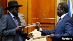 Pemimpin pemberontak Sudan Selatan Riek Machar (kanan) dan Presiden Sudan Selatan Salva Kiir bertukan dokumen perjanjian perdamaian di Addis Ababa, Ethiopia (9/5).