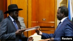 FILE - South Sudan's rebel leader Riek Machar (R) and South Sudan's President Salva Kiir (L) exchange signed peace agreement documents in Addis Ababa, Ethiopia, May 9, 2014.