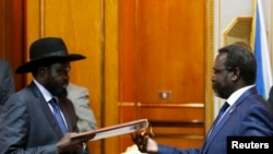 "South Sudan's rebel leader Riek Machar (R) and South Sudan's President Salva Kiir exchange a signed peace agreement in Addis Ababa, Ethiopia, May 9, 2014. Matthew Chol Jok, a displaced person in Malakal, says the country's leaders ""sign things but don't fulfill their promises."""
