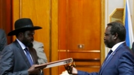 South Sudan President Salva Kiir (L) and opposition leader Riek Machar exchange an agreement signed on May 9 in Addis Ababa, recommitting to a ceasefire deal signed in January but repeatedly violated.