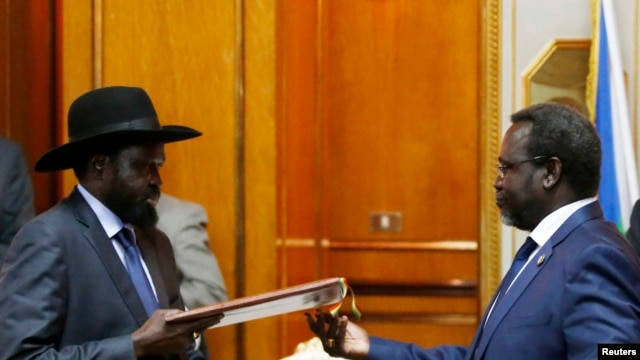South Sudan rebel leader Riek Machar (R) and President Salva Kiir (L) exchange a signed recommitment to peace in Addis Ababa on May 9, 2014. The document is one of several that have been signed but failed to end the fighting.