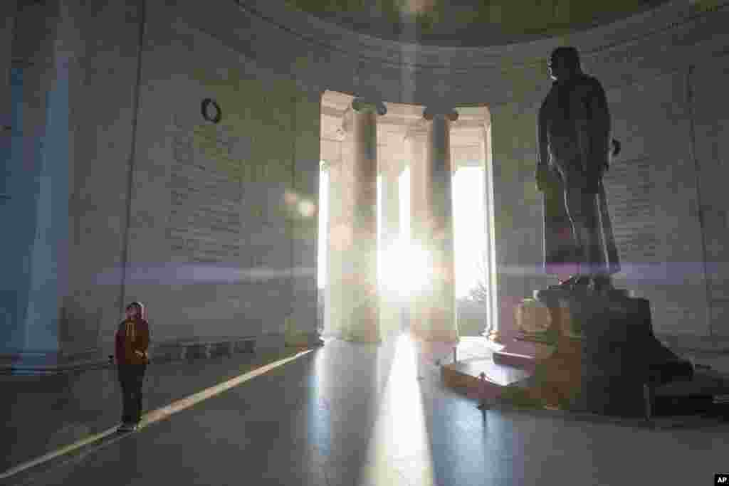 A tourist reads the inscriptions carved on the walls of the Jefferson Memorial as the early morning sun flares through the columns during the Presidents Day holiday in Washington, D.C.