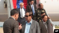 Cambodian Prime Minister Hun Sen, center, talks with an official as Tea Banh Tea Banh, lower right, Deputy Prime Minister and Minister of National Defense, deplanes upon their arrival from a trip to Laos, at the airport, in Phnom Penh, Cambodia, Saturday, Aug. 12, 2017. Cambodian Prime Minister Hun Sen, who threatened Friday to use force over a border crisis with neighboring Laos, has announced less than 24 hours later that he has peacefully resolved it. (AP Photo/Heng Sinith)