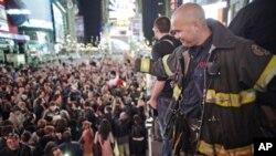 បុគ្គលិកពន្លត់អគ្គីភ័យម្នាក់បក់ដៃទៅកាន់ហ្វូងមនុស្សដែលបានមកប្រមូលផ្តុំគ្នានៅទីលានថែមស៍សាឃ្វែរ (Times Square) ក្នុងបូរីញូវយ៉ក ដើម្បីប្រារព្ធពិធីអបអរសាទរភ្លាមៗនិងមិនមានការរៀបចំទុកជាមុនមួយ កាលពីថ្ងៃច័ន្ទទី០២ខែ