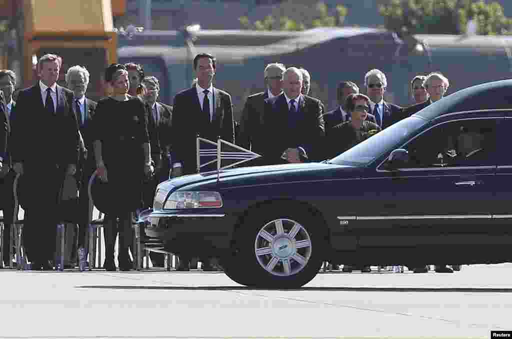 King Willem Alexander, Queen Maxima of the Netherlands, Dutch Prime Minister Mark Rutte and officials look at the convoy of hearses with the remains of the victims of Malaysia Airlines MH17 as it leaves Eindhoven airport to a military base in Hilversum, J
