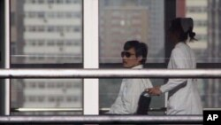 TOPSHOTS Chinese activist activist Chen Guangcheng (L) is seen in a wheelchair pushed by a nurse at the Chaoyang hospital in Beijing on May 2, 2012. A US official said there would be no repeat of the incident involving the activist Chen Guangcheng, but