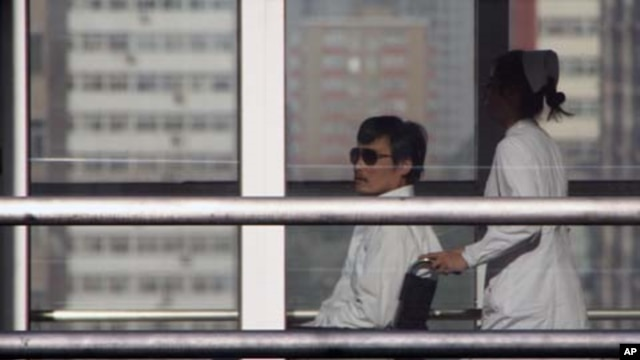 Chinese activist activist Chen Guangcheng (L) is seen in a wheelchair pushed by a nurse at Chaoyang hospital in Beijing, May 2, 2012.