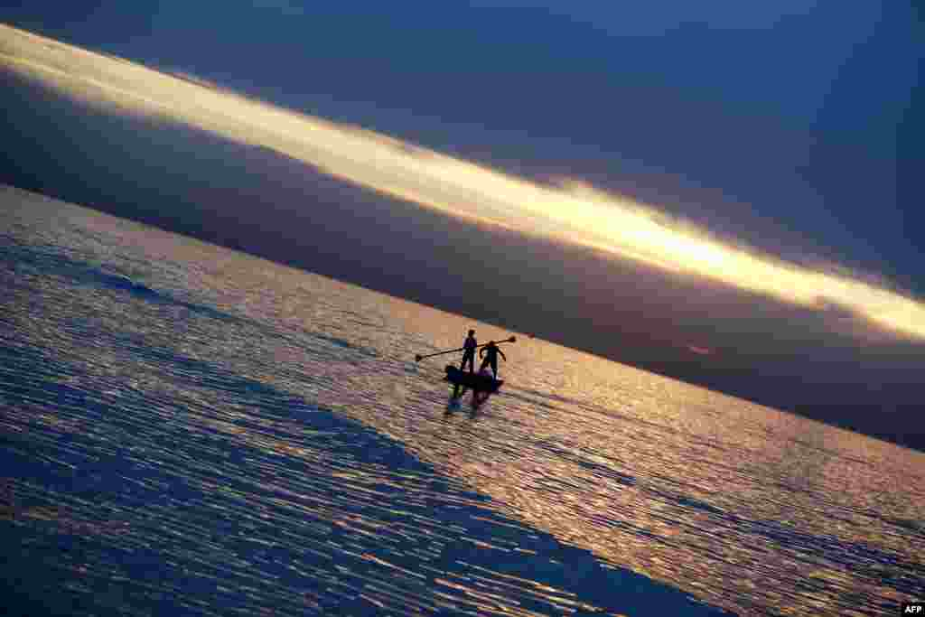 Palestinian youths on a small boat fish at sunset in Gaza City.
