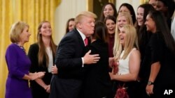 FILE - U.S. President Donald Trump hugs a member of the Oklahoma Women's Softball team as he greets members of Championship NCAA teams at the White House in Washington, Nov. 17, 2017. A new book by author Nina Burleigh will focus on Trump's relationships with women.