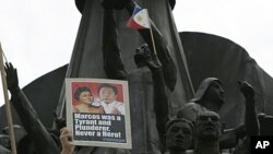A protester displays a placard with photos of the late Ferdinand Marcos and his wife Imelda at the People Power Monument opposing the proposal to bury the late dictator at the Heroes Cemetery, June 18, 2011, in suburban Quezon City, north of Manila