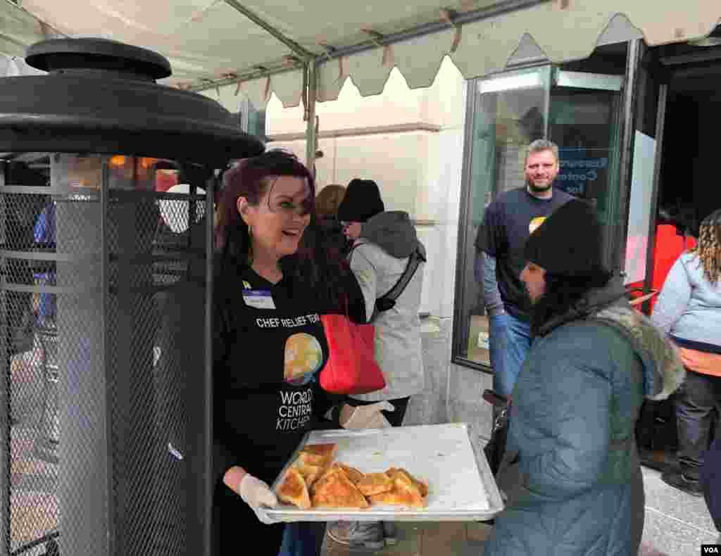 联邦政府部分关门状态进入第33天,慈善组织世界中央厨房的志愿者为排长队领取免费午餐的无薪联邦员工分发热甜点。