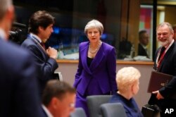 FILE - British Prime Minister Theresa May, center, arrives for a round table meeting at an EU summit in Brussels, Oct. 18, 2018.