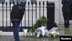 A man looks at floral tributes and messages left outside the home of former British prime minister Margaret Thatcher in London, April 9, 2013.