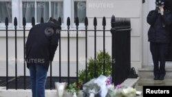 Seorang pria mengamati bunga yang ditinggalkan warga di depan rumah mantan PM Inggris Margaret Thatcher. Sementara sebagian warga Inggris berduka, banyak juga yang gembira atas meninggalnya Thatcher.