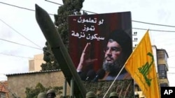Lebanese Hezbollah fighters stand next to a mock rocket under a poster of Hezbollah's leader Sheik Hassan Nasrallah. (AP Photo/Mohammed Zaatari)