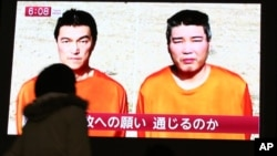 Sebuah layar televisi di Tokyo menyiarkan berita mengenai dua warga Jepang yang disandera ISIS (23/1).