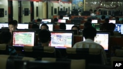 FILE - Customers surf the Internet at an Internet cafe in Beijing, China.