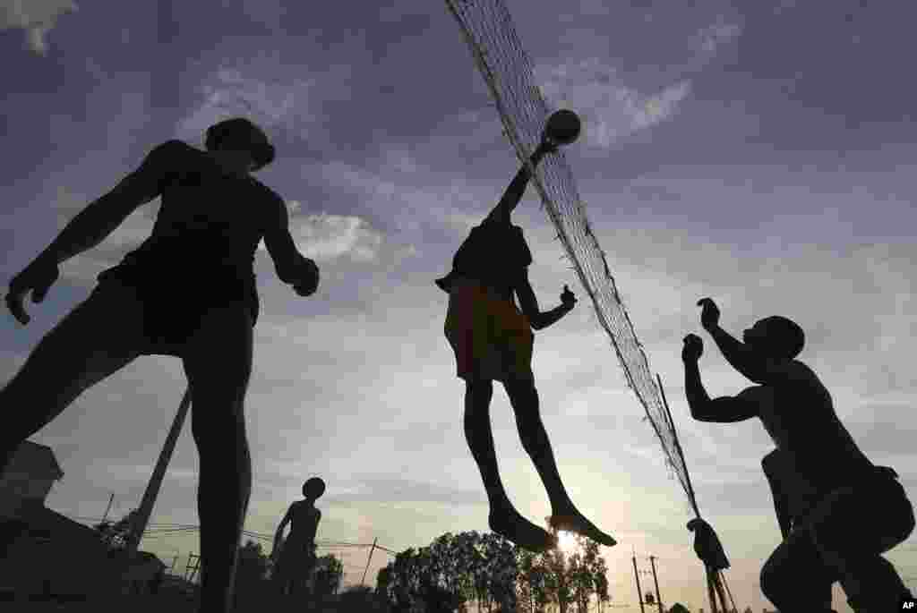 Local construction workers are silhouetted as they play volleyball after work near a construction site at Prey Mou village outside Phnom Penh, Cambodia.