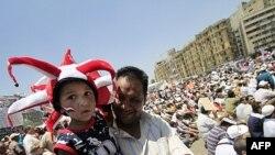 Một người mang theo đứa con trai tham gia cuộc biểu tình ở Quảng trường Tahrir trong thủ đô Cairo của Ai Cập