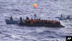 FILE: Migrants receive help from two raft from the Italian Navy ship Libra, off the Sicilian island of Lampedusa Saturday, Oct.12, 2013.