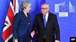 Jean-Claude Juncker, a la derecha, se prepara para dar la mano a la primera ministra británica, Theresa May, antes de su reunión en la sede de la Comisión Europea en Bruselas, Bélgica. Foto de archivo.