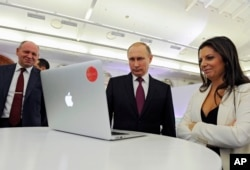 FILE - Russian President Vladimir Putin and Editor-in-chief of RT (Russia Today) 24-hour English-language TV news channel, Margarita Simonyan, attend an exhibition marking RT's 10th anniversary in Moscow, Russia.