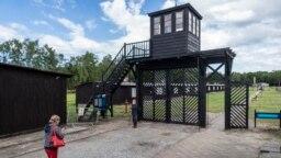 """Pengunjung memandangi """"Gate of Death"""" (Gerbang Kematian) saat mengunjungi museum Stutthof, bekas Kamp Kematian Nazi, di Sztutowo, 21 Juli 2020. (Wojtek RADWANSKI / AFP)"""