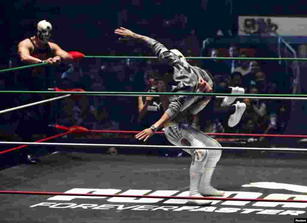 អ្នកបើកបររថយន្ត Formula One របស់ក្រុម Mercedes លោក Lewis Hamilton (ខាងស្តាំ) មកពីអង់គ្លេសសម្តែងជាមួយនឹងក្រុមកីឡាករចំបាប់ម៉ិកស៊ិកនៅកីឡាដ្ឋាន Coliseo Arena ក្នុងរដ្ឋធានី Mexico City នៅថ្ងៃទី២៨ ខែតុលា ឆ្នាំ២០១៥។