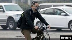 중국 베이징의 시민이 대기오염을 차단하기 위한 산소마스크를 끼고 자건거를 타고 있다. (자료사진)