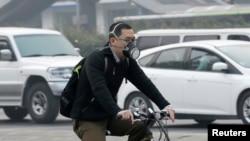 Stanovnik Pekinga vozi bicikl sa maskom da bi se zaštitio od smoga.