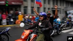 Motorcyclists waving a Venezuelan flag attend a rally in support of Venezuela's President Nicolas Maduro in Caracas, Feb. 24, 2014.