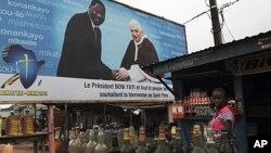 អ្នកលក់ដូរម្នាក់ឈរជិតផ្ទាំងរូបភាពដែលប្រកាសឲ្យដឹងអំពីទស្សនកិច្ចរបស់សម្តេចប៉ាបនៅសប្តាហ៍នេះទៅកាន់រដ្ឋធានី ខុនតូនូ ប្រទេសបេនីន ថ្ងៃទី១៦ វិច្ឆិកា ២០១១។ Pope Benedict XVI បានមកដល់ក្រុងបេនីននៅថ្ងៃសុក្រ ក្នុងដំណើរទស្សនកិច្ចបីថ្ងៃ ដែលជាល