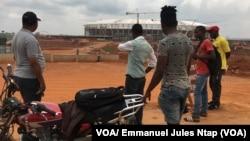 Des Camerounais observent l'etat d'avancement des travaux sur le site du stade d'Olembé. (VOA/ Jules Emmanuel Ntap)