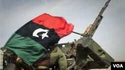 Un combatiente de la oposición cuubierto del sol con la bandera rebelde, en su puesto durante uno de los enfrentamientos en Ras Lanuf.