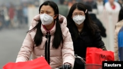 Girls wearing masks ride bicycles amid the heavy haze in Beijing February 22, 2014.