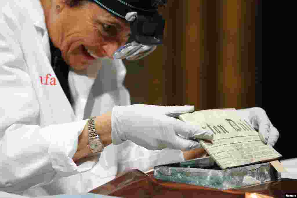 Conservator Pam Hatchfield removes a newspaper from a time capsule, which was placed under a cornerstone of the State House in 1795, at the Museum of Fine Arts, Boston, Massachusetts. The capsule was placed by a group of the U.S. founding fathers including Samuel Adams, then the state's governor, and patriot Paul Revere.