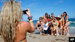 A group of spring break revelers pose for a photograph on the beach, Tuesday, March 17, 2020, in Pompano Beach, Fla.
