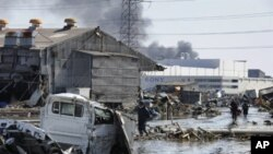 Local residents walk though a devastated street in Tagajo, Miyagi prefecture on March 13, 2011 following a massive earthquake and tsunami on March 11. Japan battled a feared meltdown of two reactors at a quake-hit nuclear plant, as the full horror of the