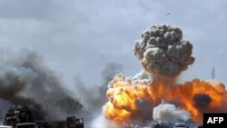 Xe cộ của lực lượng trung thành với nhà lãnh đạo Libya Moammar Gaddafi phát nổ sau cuộc không kích do lực lượng liên minh thực hiện trên một con đường giữa Benghazi và Ajdabiyah, ngày 20/3/2011