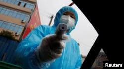 Медпрацівник перевіряє температуру пасажира авто на пункті пропуску у китайській провінції Аньхой, 6 лютого 2020. REUTERS/Thomas Peter