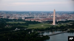In this June 7, 2021, photo taken from the window of an American Airlines aircraft the Washington Monument is seen during a flight from Phoenix to Ronald Reagan Washington National Airport.