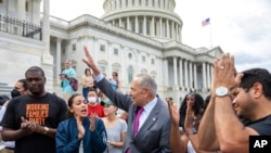 From left, Rep. Mondaire Jones, D-N.Y., Rep. Alexandria Ocasio-Cortez, D-N.Y. and Senate Majority Leader Chuck Schumer, D-N.Y., celebrate the announcement that the Biden administration will enact an eviction moratorium, at Capitol Hill, Aug. 3, 2021.