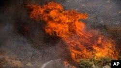 지난 2일 소방수가 캘리포니아 주 리버사이드 카운티 배닝에 퍼진 산불을 끄고 있다.