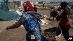 Žene nose kante napunjene prerađenom ribom na plaži Bargny, nekih 35 kilometara istočno od Dakara, Senegal, 25. travnja 2021.