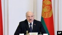 Belarus President Alexander Lukashenko speaks during a cabinet meeting in Minsk, Belarus, July 23, 2021. Belarusian authorities have ramped up raids and arrests of independent journalists and civil society activists in recent weeks.
