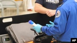 FILE-A Transportation Security Administration (TSA) official checks a passenger's carry-on luggage at a security checkpoint at Hartsfield-Jackson Atlanta International Airport in Atlanta.